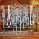 The warp chains hanging from the loom.