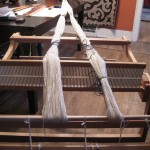 """The 200 thread warp has been measured.  It is anchored to the table with a """"c-clamp"""" at one end and looped over the apron rod at the other to hold it in place temporarily."""