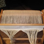 At this point, the entire warp has been wound onto the warp beam.  Thread ends are hanging from the heddle in front waiting for 1 of the 2 threads in the heddle slot to be threaded through the heddle holes.