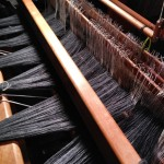 The front of the loom showing the warp ends through the reed and heddles.
