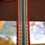 Pulling taut - Using my beater to stabilize the band, I am pulling the weft thread to the right.