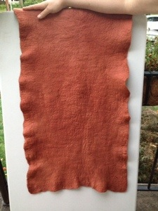 The madder dyed felt sheet with my arm for scale.  Notice the lovely pebbly texture.
