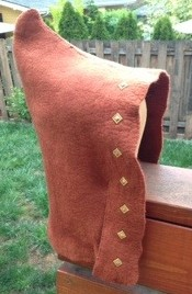 Side view of the hat showing the pointy bit on the crown and the shoulder flaps.